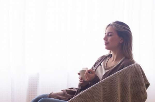 Winter vibes. Young peaceful woman enjoying cocoa near window at home, panorama, empty space